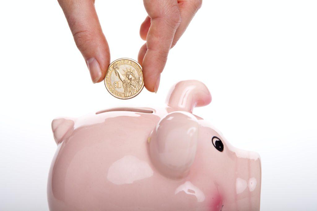 putting a coin into a piggy bank